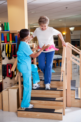 African American physical therapist (40s) working with senior patient (80s) walking down stairs.